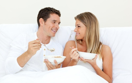 Affectionate couple having breakfast lying on their bed photo