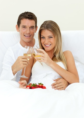 glass bed: Romantic couple drinking Champagne with strawberries
