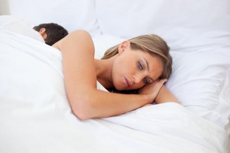 novios enojados: Pareja molesto por separado acostado en su cama  Foto de archivo