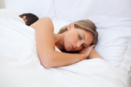 disagreement: Upset couple lying separately on their bed  Stock Photo
