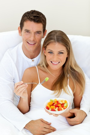 Romaantic couple eating fruit lying on their bed  photo