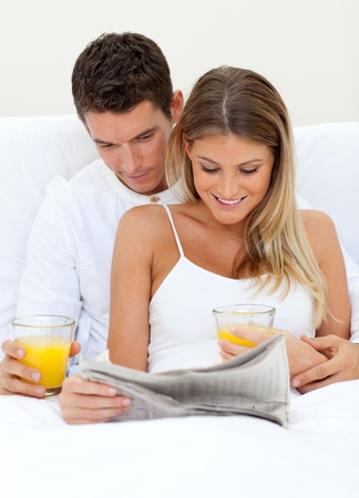 Lovers reading a newspaper and drinking orange juice photo