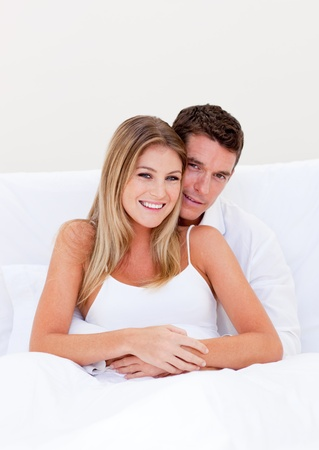 enamored: Portrait of an enamored couple sitting on bed