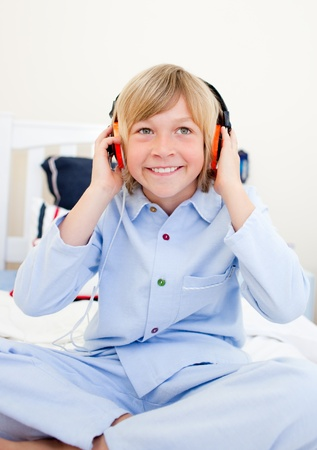 Laughing boy listening music sitting on bed photo