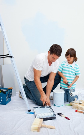 Lively Father and his son painting in their new house photo