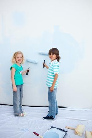 Cute siblings painting a wall  photo
