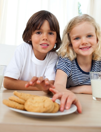 biscuits: Cute siblings eating biscuits  Stock Photo