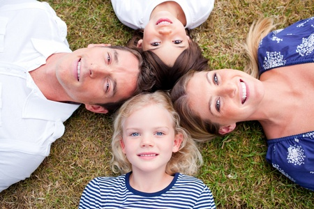 Loving family lying in circle on the grass photo