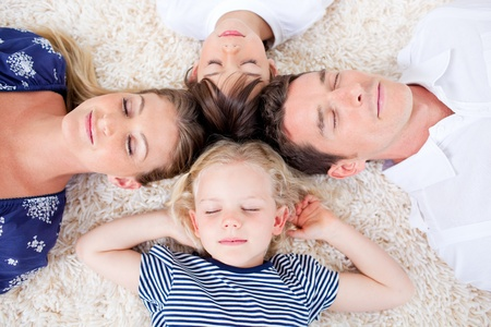 Relaxed family lying in circle on the wall-to-wall carpet photo