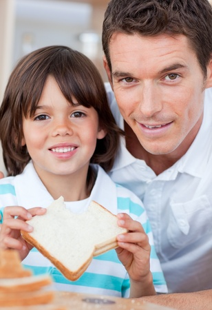 Portrait of a little boy and his father eating bread Stock Photo - 10244880