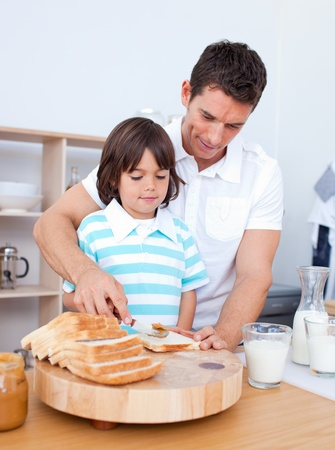 slices of bread: Charming father and his son spreading jam on bread