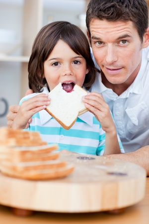 Cute little boy and his father eating bread photo