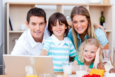 Loving family using laptop during the breakfast photo