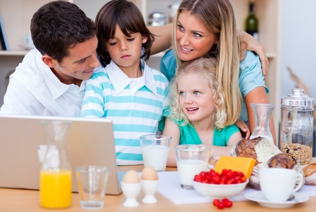 blissful: Blissful family using laptop during the breakfast