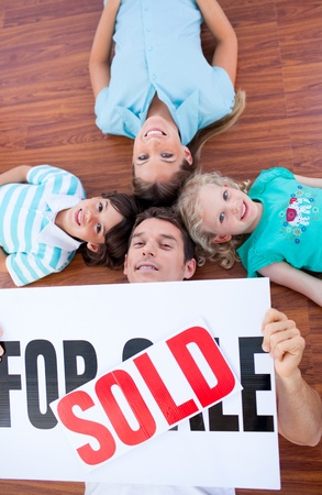 Happy family lying on floor after buying a house photo