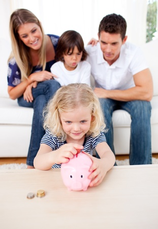 Adorable little girl inserting coin in a piggybank photo