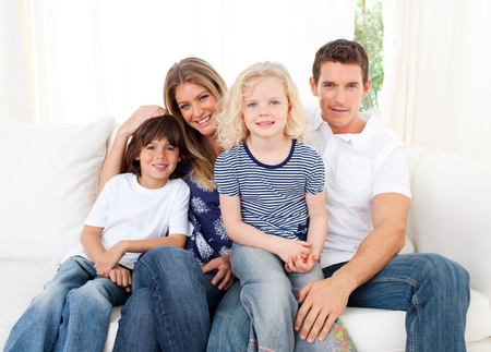 Joyful family watching television sitting on sofa photo