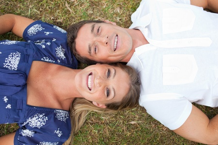 Happy couple lying on the grass  photo