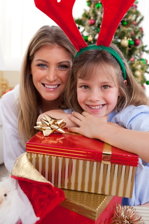 Portrait of a mother and her daughter holding Christmas presents photo