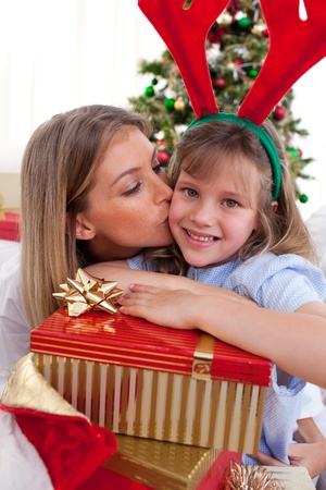 Loving mother kisses daughter at Christmas photo