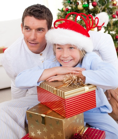 Smiling father and his son holding Christmas gifts photo