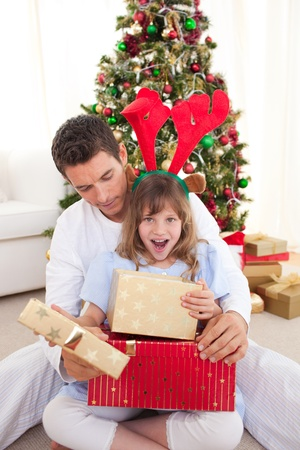 Surprised little girl opening presents with her father Stock Photo - 10240425