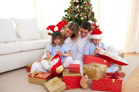 Portrait of a happy family opening Christmas gifts photo