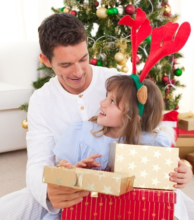 Portrait of a smiling father and his daughter opening Christmas presents  photo