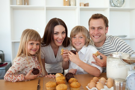 Cute children eating muffins with their parents photo