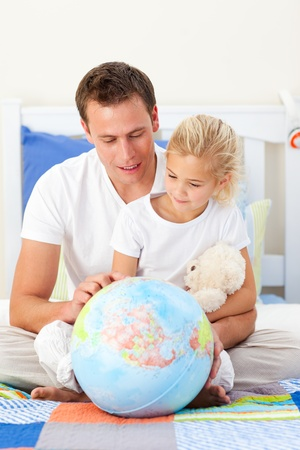 Attentive father and his daughter looking at a terretrial globe photo