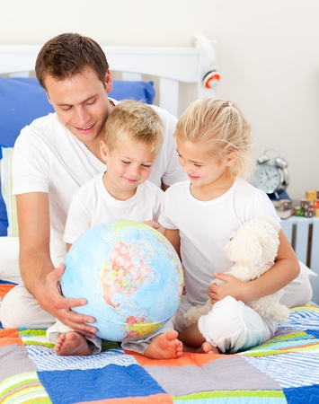 Jolly father and his children holding a terretrial globe  photo