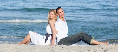 Portrait of couple sitting on sand photo
