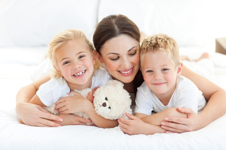 kids hugging: Cheerful children with their mother lying on a bed Stock Photo