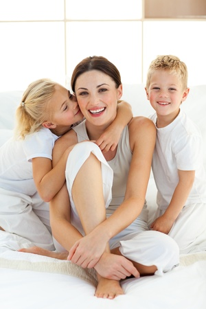 Cute children kissing their mother sitting on a bed