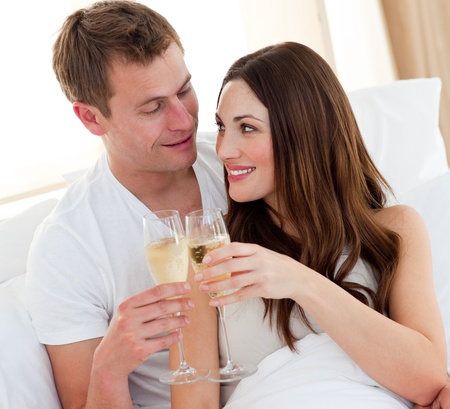 Romantic couple drinking champagne lying in bed photo