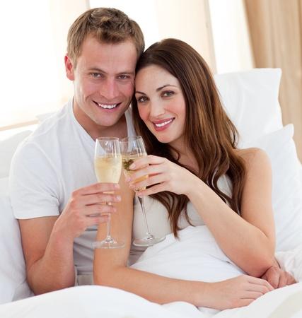 couple amoureux: Aimant champagne boire de couple gisant au lit
