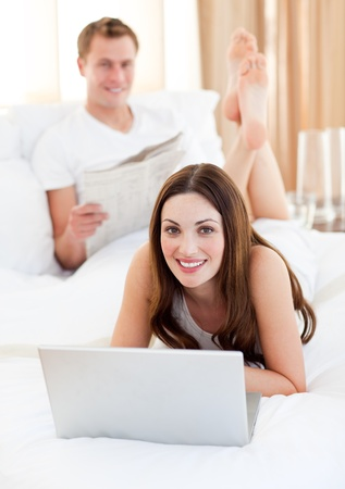 Smiling couple having activites lying on bed photo
