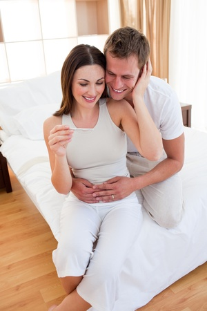 Blissful couple finding out results of a pregnancy test photo