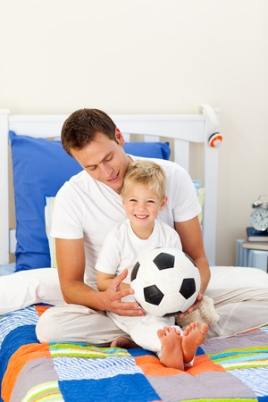 Cute little boy and his father playing with a soccer ball photo