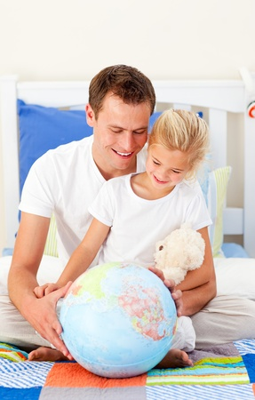 Earing father and his daugther looking at a terrestrial globe photo
