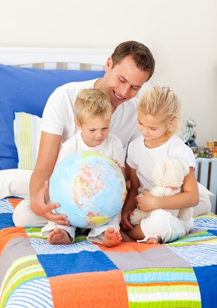 chirpy: Blond siblings and their father looking at a terrestrial globe