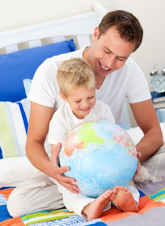 gratified: Merry father and his son looking at a terrestrial globe