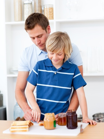 Loving father helping his son prepare the breakfast photo