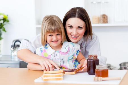 Attentive mother helping her daughter prepare the breakfast Stock Photo - 10258655
