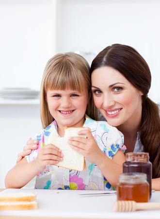 Charming mother and her daughter having breakfast photo