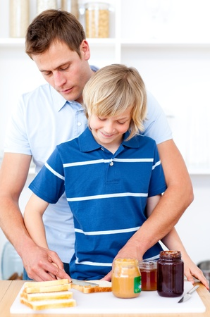 Adorable boy and his father preparing breakfast