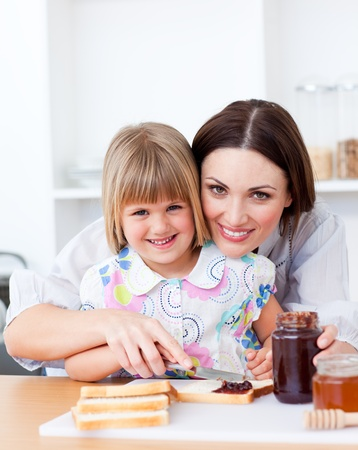 Cute little girl and her mother preparing toasts photo
