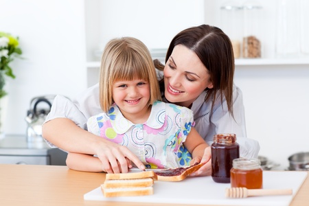 Smiling little girl and her mother preparing toasts Stock Photo - 10258715