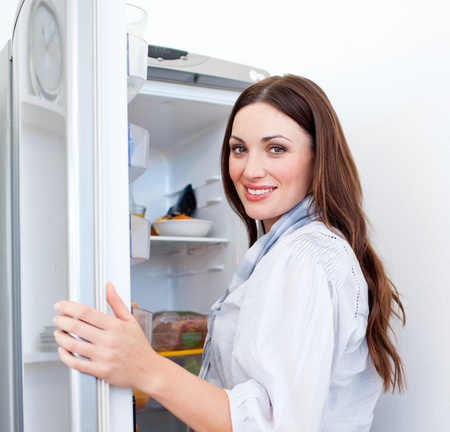 Happy woman looking for something in the fridge photo