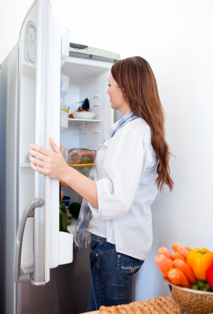 Attractive woman looking for something in the fridge photo